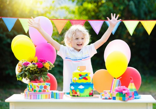 little girl enjoying her birthday party with balloons and presents